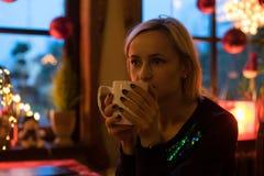 画象一年轻舒适与咖啡、曲奇饼和圣诞灯和杉木分支 免版税图库摄影