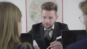 画象三同事在桌上,人,并且妇女是在笔记本附近 介入工作人们 股票录像
