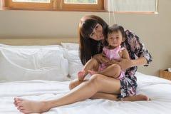 画象亚裔美丽的母亲和逗人喜爱的婴孩是幸福 免版税图库摄影