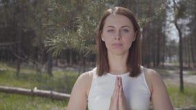 画象优美的逗人喜爱的妇女用祈祷的手将在惊人的壮观的绿色森林里祈祷 股票录像