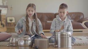 画象俏丽的可爱的兄弟和扮演音乐家的姐妹孪生打罐和盘与大匙子和笑 股票录像