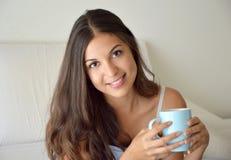 画象俏丽的女孩饮用的咖啡或茶在床上早晨在公寓与拷贝空间 免版税库存图片