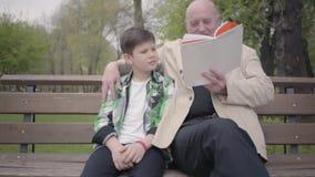 画象可爱的祖父和孙子在公园坐长凳,读男孩的老人书 股票录像
