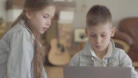 画象可爱的集中的男孩是键入或使用在膝上型计算机和他的观看与兴趣的双姐妹什么 股票录像
