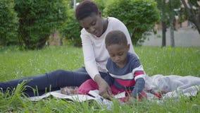 画象可爱的非裔美国人的妇女坐有她的小儿子的毯子在公园 年轻母亲尝试 股票录像