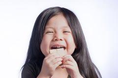 画象吃在孤立白色的一个逗人喜爱的矮小的亚裔女孩薄酥饼 库存照片
