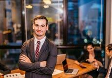画象商人微笑的工作在现代顶楼办公室在晚上 免版税库存照片