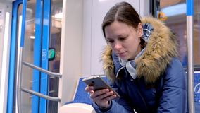 画象在一块空的地铁的疲乏的妇女乘驾和浏览在她的智能手机 正面图 影视素材
