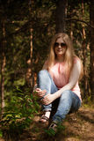 画象女孩佩带的太阳镜坐绿草 图库摄影