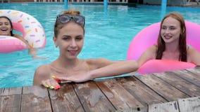 画象女孩游泳与桃红色可膨胀的圆环的在游泳池边,朋友游泳入与大海的游泳池 股票录像