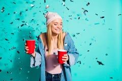 画象她她在手中拿着两个红色杯子的nice-looking迷人的逗人喜爱的可爱的可爱的甜迷人的爽快女孩 库存图片