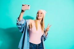 画象她她nice-looking可爱的可爱的快乐的爽快采取selfie的女孩佩带的streetstyle衣物 免版税图库摄影