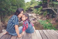 画象妇女和孩子smilling和坐有河水小河的木桥在背景中 免版税库存图片