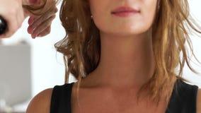 画象少妇,当卷曲子线使用头发铁在秀丽演播室时 关闭做发型与的美发师 影视素材