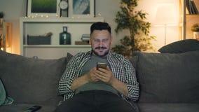 画象年轻人使用智能手机的和微笑的在家坐在晚上 股票视频