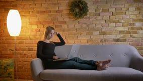 画象年轻俏丽女性千福年观看在膝上型计算机的一部电影和快乐地笑,当坐时 股票录像