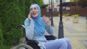 画象年轻回教妇女残疾在一条传统围巾在坐在的一个轮椅的智能手机沟通 影视素材