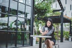 画象年轻女实业家用途手机,当坐i时 免版税库存照片