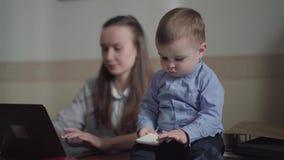 画象年轻母亲女实业家工作在与膝上型计算机的办公室桌上的和可爱的男婴坐桌和 股票录像