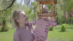 画象年轻母亲消费时间在有她的女儿的公园 举她的女孩,因此她的妇女可能看 影视素材