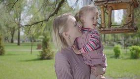 画象年轻白肤金发的母亲举行可爱的小女儿和在惊人的绿色公园显示她的鸟饲养者房子 ?? 股票视频
