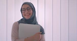 画象愉快地举行膝上型计算机微笑的俏丽hijab的回教女实业家和玻璃入照相机 股票录像