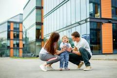 画象愉快的三口之家 年轻父母微笑的使用与他们的小女儿,当走通过街道时 免版税库存图片