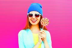 画象愉快的微笑的妇女拿着在棍子的一个棒棒糖在桃红色 免版税图库摄影