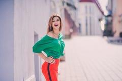 画象时尚时髦性感年轻行家白肤金发的妇女、典雅的夫人、绿色上面和红色裙子,凉快的女孩 城市视图urb 库存图片