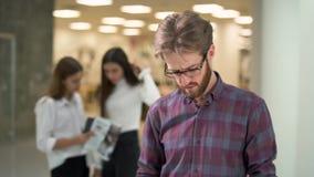 画象有一个胡子的一个人在玻璃和偶然格子衬衫读书文件与站立在大厅的销售报告 股票视频