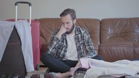 画象有胡子的人坐地板和包装的手提箱 准备的概念旅途的 ?? 股票视频