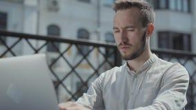 画象有胡子的年轻人在桌上坐在膝上型计算机前面的大阳台,运转 概念的自由职业者 股票视频