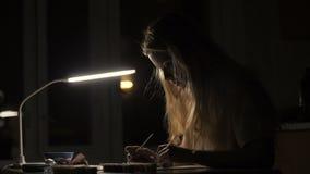 画象浸洗在油漆的妇女艺术家刷子画的在册页在暗室 股票录像