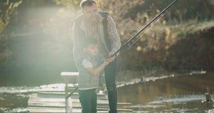 画象爸爸鼓励了他的儿子对钓鱼在湖在好日子,一起度过好片刻 股票录像