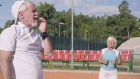画象生气成熟夫妇丢失了在网球场的比赛 拿着头用手的老人和妇女 影视素材