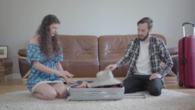 画象男人和妇女在家坐地板在一个皮革沙发前面,包装手提箱在旅行前 ?treadled 股票录像