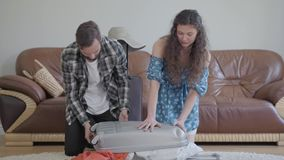 画象男人和妇女在家坐地板在皮革沙发前面,包装手提箱在旅行前 ?? 影视素材