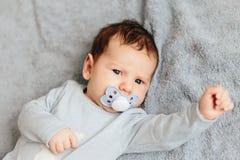 画象男婴恼怒,愤怒,皱眉的和积极躺在床上 ????? 免版税库存照片