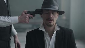 画象确信的人坐在浅顶软呢帽帽子的椅子和走从后面的其他人与枪并且射击他在头 影视素材