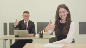 画象确信的年轻坐在书桌的男性和女性经理在办公室 显示赞许的男人和妇女 股票视频