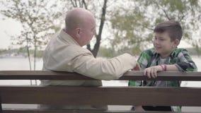 画象祖父和孙子在公园在河附近坐长凳,老人讲有趣故事 股票录像