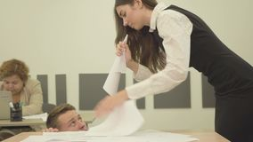 画象紧张的恼怒的年轻女人折叠了纸以垫铁的形式和叫喊在坐在桌下的人 股票视频