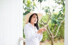 画象美丽的亚洲女性固定的单元电话和微笑对室外,正面认为,好态度 免版税图库摄影