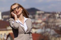 画象美好白肤金发谈话在电话 妇女佩带的衣服和玻璃 免版税库存照片