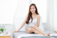 画象美好的年轻亚洲妇女开会和在卧室微笑窗口 免版税库存照片