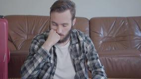 画象英俊的迷茫的有胡子的人在家坐地板在皮革沙发前面的手提箱附近,很多 影视素材