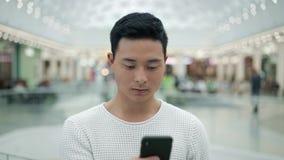 画象被射击在大购物中心背景的亚洲男性移动的电话 股票视频