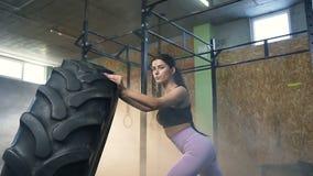 画象被射击拿着大拖拉机轮胎的体育确信的妇女在健身房的交叉训练期间 股票视频