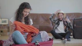 画象让坐在前景的手提箱的被触犯的妇女烦恼,当她愉快的丈夫包装的材料以前时 股票录像