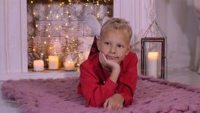 画象说谎在圣诞节壁炉背景的舒适地毯的少年男孩 股票录像